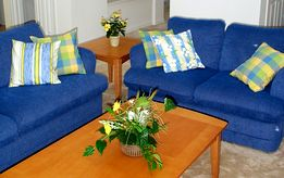 Blue sofa with yellow and cream cushions