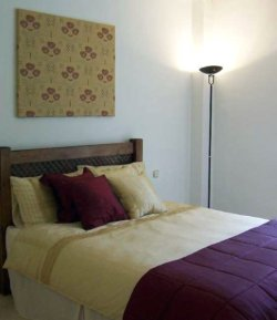 Red and gold bedding with fabric wall panel